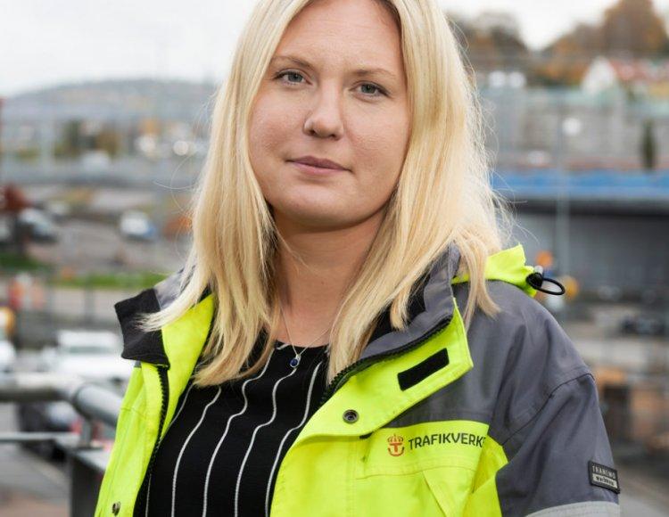 Jenny Karlsson står utomhus med en byggarbetsplats i bakgrunden.
