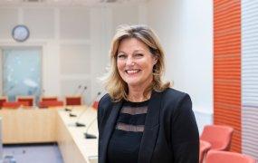 En glad Carina Norrwie Strömstedt, HR-strateg på Region Västmanland ståendes i ett av konferensrummen klädd i svart kostym och svart blus.