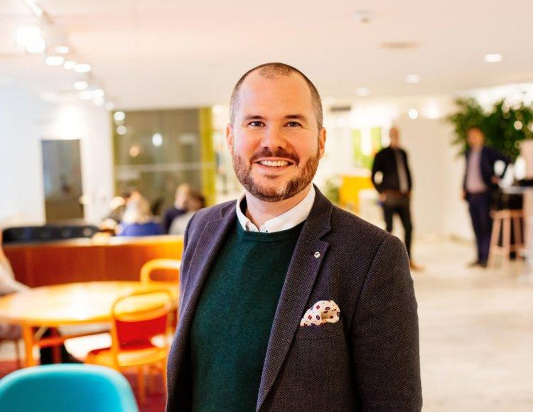 Robin Gustafsson står på  ett utav Folksams kontor med sittgrupper och kollegor i bakgrunden.